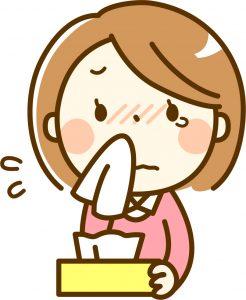 花粉症で鼻をかんでいる20代女性