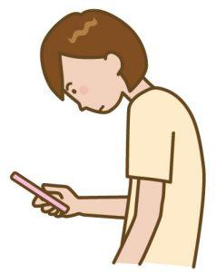 スマートフォンを見る姿勢の悪い女性