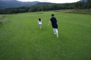 子供と草原を走る女性